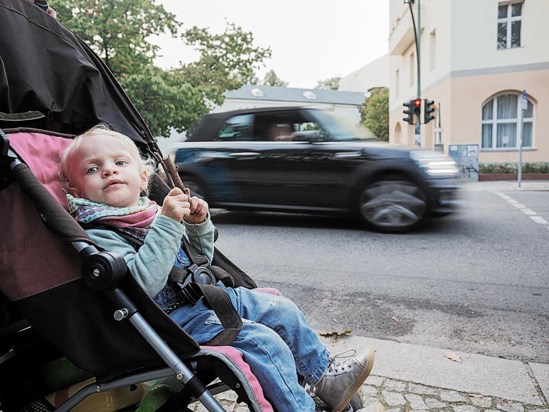 Ein kleines Kind sitzt im Kinderwagen am Straßenrand