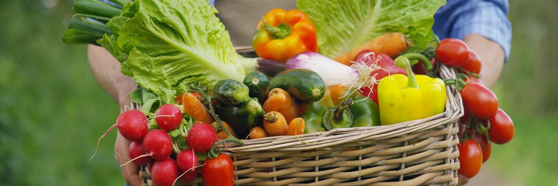 Ein Mann trägt eine Kiste gefüllt mit frischem Gemüse.