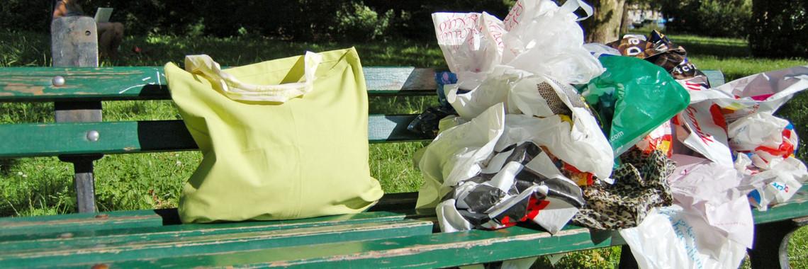 Auf einer Bank steht eine Mehrwegtüte und daneben liegt ein Stapel Plastiktüten.